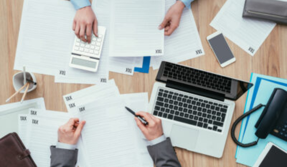 Business people working at office desk, they are checking tax forms and calculating costs, finance and management concept
